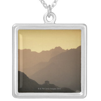 A setting sun filters through a sandstorm from square pendant necklace