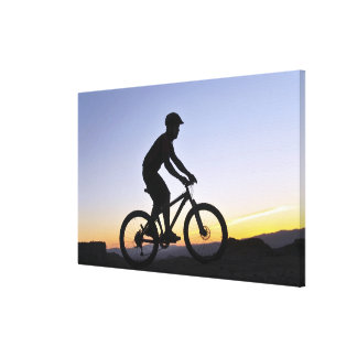 A silhouette of a mountain biker at sunset on canvas print