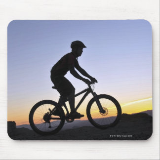 A silhouette of a mountain biker at sunset on mouse mat