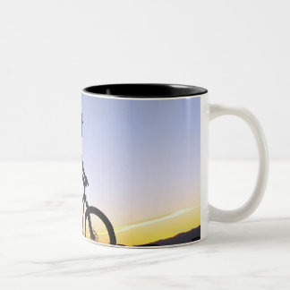 A silhouette of a mountain biker at sunset on Two-Tone coffee mug