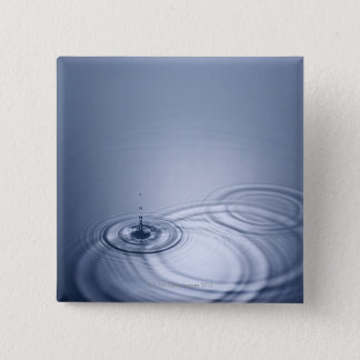 A single droplet of water falling into a calm 15 cm square badge