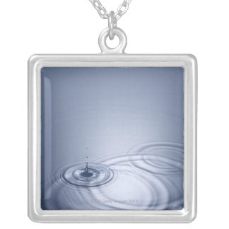 A single droplet of water falling into a calm silver plated necklace