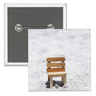 A small chair in the sandy beach 15 cm square badge