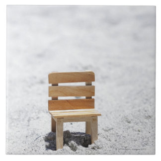 A small chair in the sandy beach tile