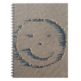 A smiley face drawn in sand. notebook