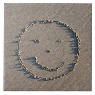A smiley face drawn in sand. tile