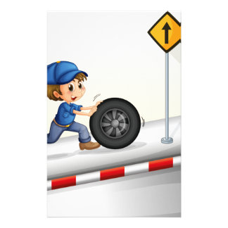 A smiling mechanic pushing the tire stationery