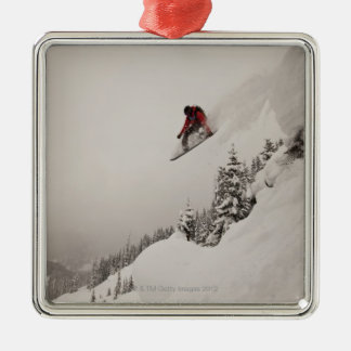 A snowboarder jumps off a cliff into powder in christmas ornament