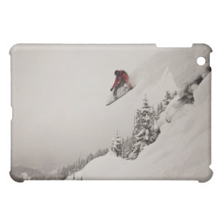 A snowboarder jumps off a cliff into powder in cover for the iPad mini