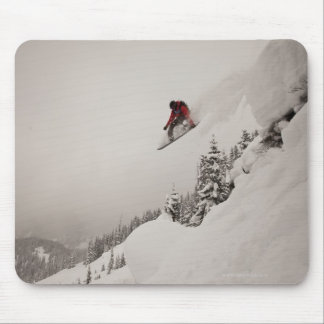 A snowboarder jumps off a cliff into powder in mouse mat