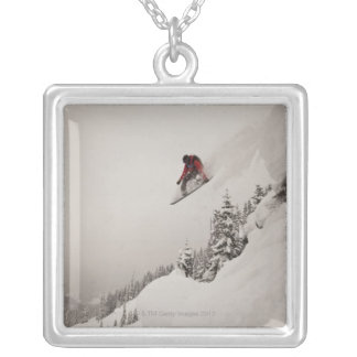 A snowboarder jumps off a cliff into powder in silver plated necklace