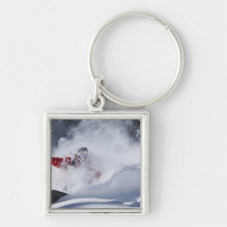 A snowboarder rips untracked powder turns in Silver-Colored square key ring