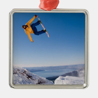 A snowboarder spins off a jump in Argentina Ornament