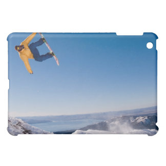 A snowboarder spins off a jump in Argentina iPad Mini Covers