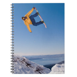 A snowboarder spins off a jump in Argentina Notebook