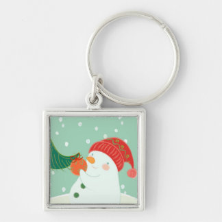 A snowman hanging an ornament on a tree Silver-Colored square key ring