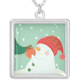 A snowman hanging an ornament on a tree silver plated necklace