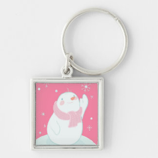 A snowman reaching for a falling snowflake key ring