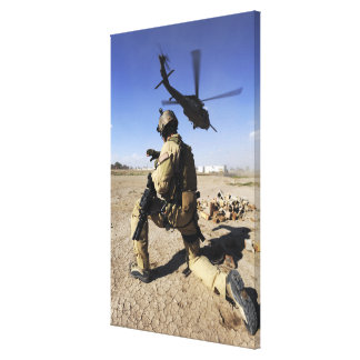 A soldier conducts security for an HH-60 Canvas Print