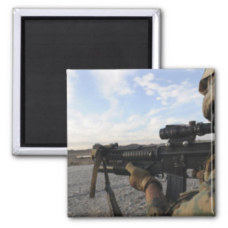 A soldier sights in to fire on a target square magnet