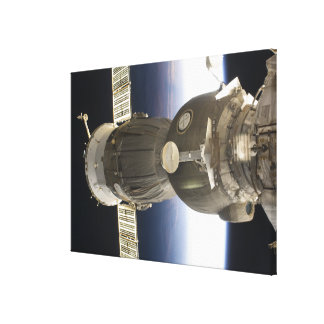 A Soyuz spacecraft backdropped by Earth Canvas Print