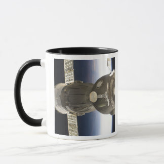 A Soyuz spacecraft backdropped by Earth Mug