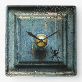 A spider on a grunge blue turquoise antique door square wall clock