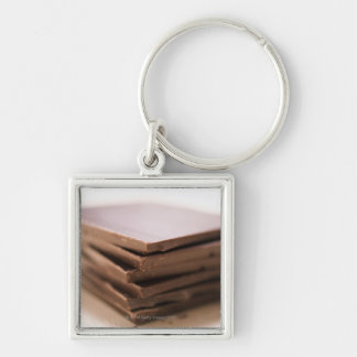 A stack of baker's chocolate ready to be chopped Silver-Colored square key ring
