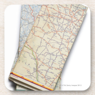 A stack of folded road maps on a white beverage coaster