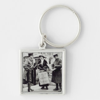 A Suffragette selling newspapers to two Key Ring