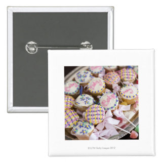 A tray of baby rattle cupcakes at a baby shower pinback buttons