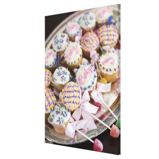 A tray of baby rattle cupcakes at a baby shower. canvas print