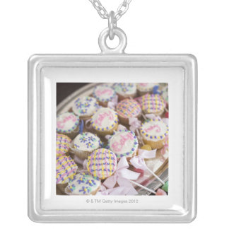 A tray of baby rattle cupcakes at a baby shower. silver plated necklace