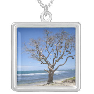 A tree decorated with old buoys on the beach in silver plated necklace