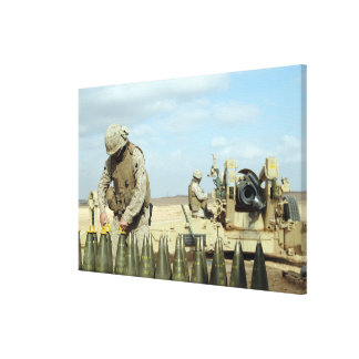 A US Marine prepares howitzer rounds to be fire Canvas Print