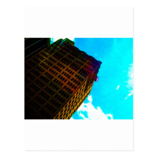 A vibrant and tall building against the  blue sky post card