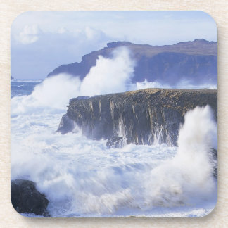 a view of the waves crashing against rocks coasters