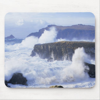 a view of the waves crashing against rocks mouse mat