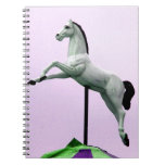 A white horse carousel statue against purple note book
