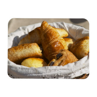 A wicker breakfast basket with croissants, and vinyl magnet