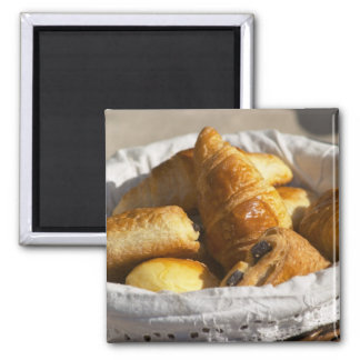 A wicker breakfast basket with croissants, and square magnet