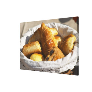 A wicker breakfast basket with croissants, and stretched canvas prints