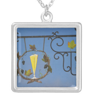 A wrought iron sign that illustrates the theme silver plated necklace