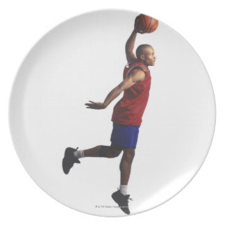 a young adult male basketball player flies plate