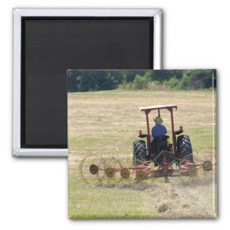 A young boy driving a tractor harvesting square magnet