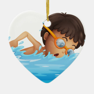A young boy swimming with a yellow goggles christmas ornament