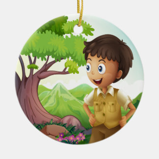A young boyscout in the forest round ceramic ornament