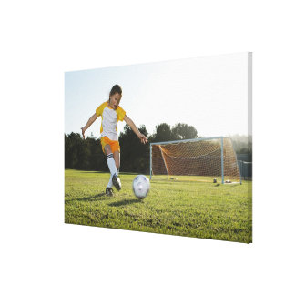 A young girl playing soccer on a soccer field in canvas print