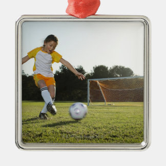 A young girl playing soccer on a soccer field in christmas ornament