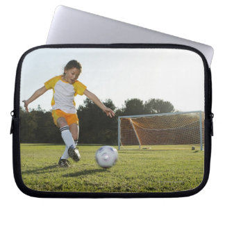 A young girl playing soccer on a soccer field in laptop sleeve